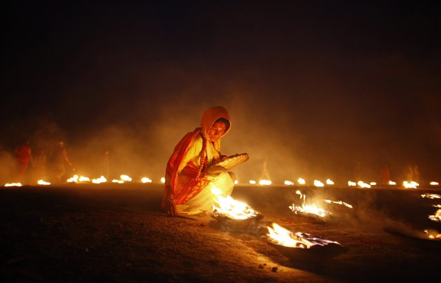 A Nepalese Hindu devotee lights an oil lamp during the last day of a Mahayagya, holy rituals that last for seven days, near Pashupatinath temple in Katmandu, Nepal, Tuesday, April 22, 2014. The Mahayagya was organized by Hindu devotees to welcome Nepali New year, for peace in Nepal and to generate income to construct a temple of Goddess Laxmi in Sankhu on the outskirts of Katmandu. (Photo by Niranjan Shrestha/AP Photo)