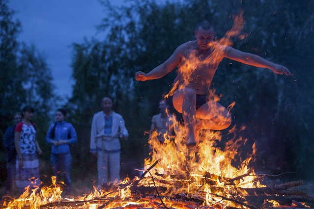 A man jumps over a campfire during a celebration of the traditional Ivana Kupala (Ivan the Bather) holiday near Omsk, Russia, July 9, 2015. (Photo by Dmitry Feoktistov/Reuters)