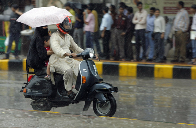 A woman (L) holds an umbrella as she travels on a scooter during rains in New Delhi July 6, 2010. (Photo by Mukesh Gupta/Reuters)