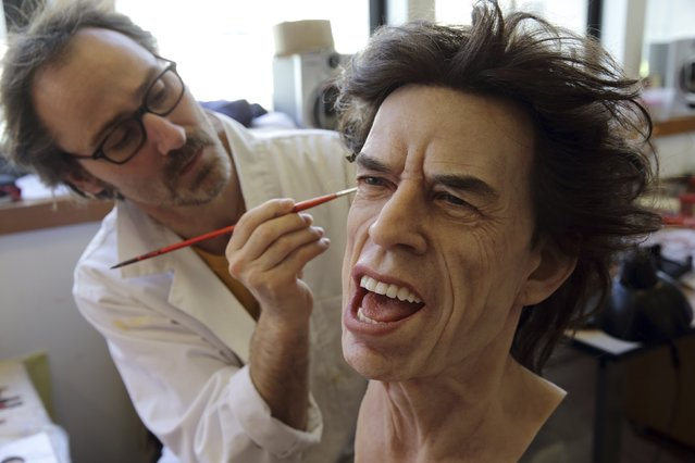 Paris' Grevin Wax Museum painter Franck Bruneau works on the head of Rolling Stones lead singer Mick Jagger at their workshop in Paris, April 9, 2014. The statue is prepared ahead of the opening of the new Grevin Wax Museum in Prague on May 1st. Fifteen artists, including sculptors, moulders, dressmakers, make-up artists, wig makers, hairdressers along with lighting and set designers and sound engineers  are involved in the creation of the hyper realistic statues.(Photo by Philippe Wojazer/Reuters)