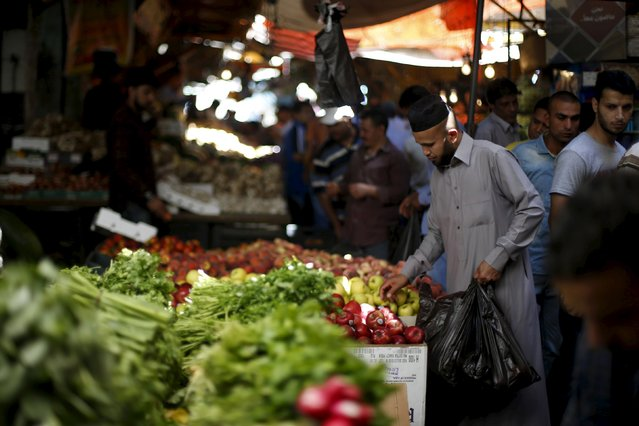 A man buys vegetables from a souk during the last week of the Muslim holy fasting month of Ramadan in Amman, Jordan, July 10, 2015. (Photo by Muhammad Hamed/Reuters)
