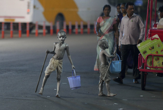 Young boys with their bodies painted and dressed as Mahatma Gandhi seek alms at a traffic intersection in Hyderabad, India, Tuesday, September 10, 2019. Millions of Indians still living on less than $2 a day. (Photo by Mahesh Kumar A./AP Photo)