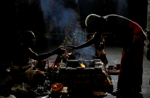A Hindu priest makes a blessing for a devotee during the annual Maha Shivaratri festival by praying and fasting for an entire day as they  hold a night-long vigil at a Hindu temple in Colombo, Sri Lanka February 24, 2017. (Photo by Dinuka Liyanawatte/Reuters)