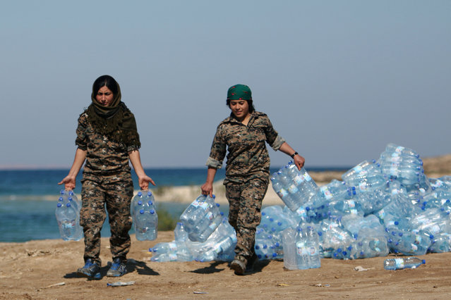 Syrian Democratic Forces (SDF) female fighters carry water supplies on the bank of the Euphrates river, west of Raqqa city, Syria April 10, 2017. (Photo by Rodi Said/Reuters)