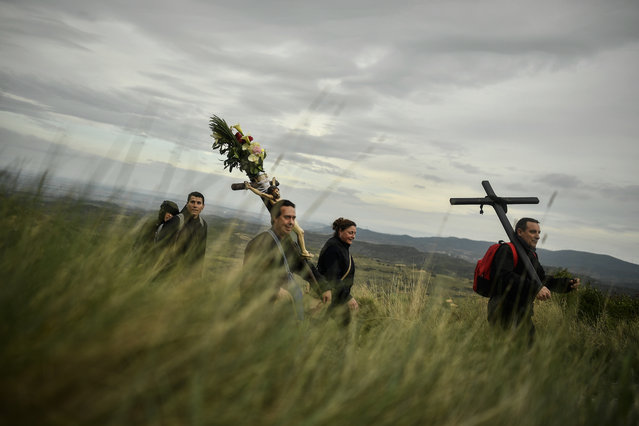 Catholic penitents of the Ujue Virgin carrying a crucifix decorated with flowers take part in a pilgrimage from Tafalla and other villages to the small town of Ujue, northern Spain, Sunday, April 30, 2017. According to tradition, the pilgrimages to Ujue originated in 1043 when the residents of Tafalla made a pilgrimage to Ujue to thank the Virgin for their victory in a battle. (Photo by Alvaro Barrientos/AP Photo)