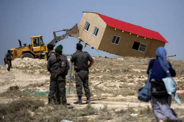 Israeli border police officers stand guard as a house is demolished in the Wesk Bank Jewish settlement of Maaleh Rehavam, Wednesday, May 14, 2014. Israel's Supreme Court ruled that the land the houses were built on belong to Palestinians. (Photo by Sebastian Scheiner/AP Photo)