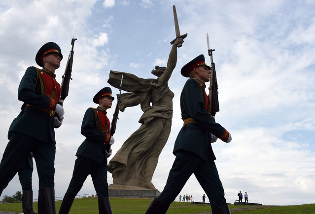 """Soldiers of the guard battalion of the Russian army pass by the statue """"The Motherland Calls!"""" at the Mamayev Kurgan memorial complex in Volgograd, Russia, 15 July 2015. The statue is part of memorial complex that commemorates the Battle of Stalingrad (today Volgograd) in the Second World War. The city on the Volga will host matches in the 2018 football World Cup. (Photo by Marcus Brandt/EPA)"""