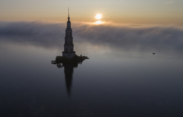 The famous Kalyazin Bell Tower, part of the submerged monastery of St. Nicholas, is seen in the morning fog in the town of Kalyazin located on the Volga River, 180 km (111 miles) north-east of Moscow, Russia, Monday, August 12, 2019. After the construction of the Uglich Dam in 1939 to form the Uglich Reservoir, the old parts of Kalyazin, including several medieval structures, were submerged under the reservoir's waters. (Photo by Dmitri Lovetsky/AP Photo)