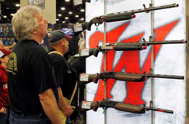Gun enthusiasts look over Winchester guns at the National Rifle Association's annual meetings and exhibits show in Louisville, Kentucky, May 21, 2016. (Photo by John Sommers II/Reuters)