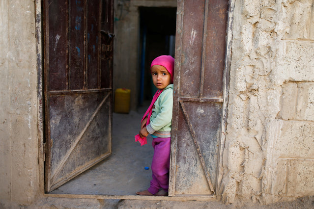 A girl stands at the door of her house during a house-to-house vaccination campaign in Sanaa, Yemen February 20, 2017. (Photo by Khaled Abdullah/Reuters)