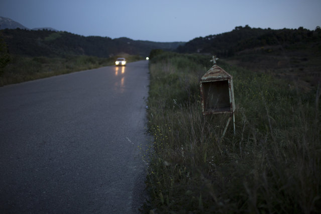 In this photo taken on Thursday, April 27, 2017, a car drives past an abandoned iron roadside shrine near the village of Kritharakia, in the Peloponnese region of southern Greece. On a long, straight stretch of rural road in southern Greece, a little reminder of death stands among the long grass. Flanked by plastic flowers and illuminated after sunset by solar-powered lights, such miniature shrines are a common sight in a country that has one of the European Union's worst road fatality rates. Made of iron sheeting, stone, wood, concrete or marble, tens of thousands of such shrines punctuate Greece's roadside scenery, usually on tricky bends or cliffside stretches – even in central Athens. In a few cases, they are offerings of thanks from motorists who escaped alive from a bad crash. Most contain religious pictures, perhaps a picture of the deceased and an oil-fuelled lamp. According to police data, 804 people died in road accidents in Greece last year and more than 13,000 were injured, placing a severe burden on the cash-strapped country's public health and welfare systems. It's the sixth-worst road fatality rate in the 28-member European Union, according to the Eurostat statistical agency. (Photo by Petros Giannakouris/AP Photo)