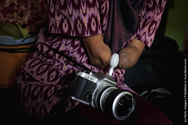 Armless professional photographer Rusidah, 44, carries out camera maintenance