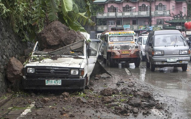 Motorists drive past a parked vehicle damaged by a landslide due to monsoon rains brought by Typhoon Ester in the mountain resort city of Baguio in northern Philippines June 10, 2014. Typhoon Ester, the first typhoon that hit Philippines after long summer months, has brought moderate to heavy rains in some parts of the country, state forecasters and local media reports said. (Photo by Harley Palangchiao/Reuters)