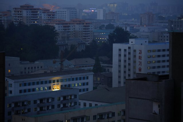 Portraits of the late North Korean leaders Kim Il Sung, left, and Kim Jong Il, right, glow on the facade of a building as dusk descends upon Pyongyang, North Korea, Friday, May 8, 2015. In Pyongyang, commercial advertisements are rarely seen in public, but portraits of the late leaders and propaganda slogans are a common sight on buildings and along the streets. (Photo by Wong Maye-E/AP Photo)