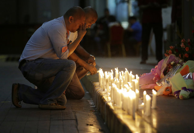A man holds back tears as he lights candles for victims in an attack at the Resorts World Manila complex, Friday, June 2, 2017, in Manila, Philippines. (Photo by Aaron Favila/AP Photo)