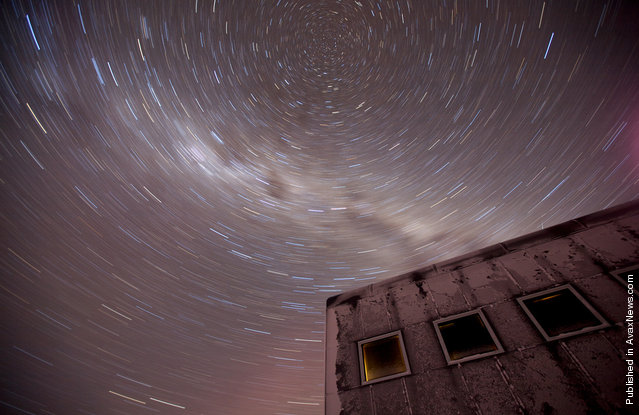 A 20-minute exposure reveals the southern celestial axis above the new elevated station at Amundsen-Scott South Pole Station on July 21, 2009. At the poles, scientists can study a fixed point in the sky for months and years, whereas in the middle latitutes the stars 'move' across the night sky. The white cloudy streak is the Milky Way