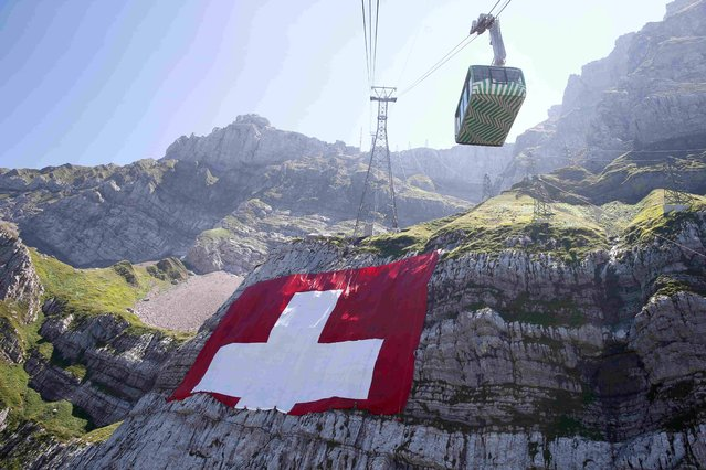 Climbers place a huge 80x80 metres (262x262 feet) Swiss national flag on the western face of the north-eastern Swiss landmark Mount Saentis, Switzerland July 31, 2015. (Photo by Arnd Wiegmann/Reuters)