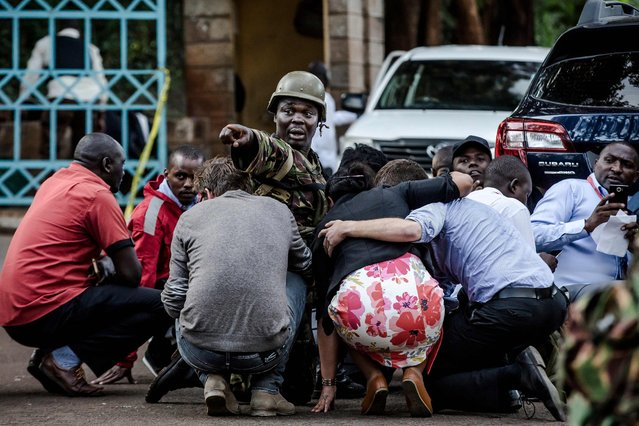 Special forces protect people at the scene of an explosion at a hotel complex in Nairobi's Westlands suburb on January 15, 2019, in Kenya. A huge blast followed by a gun battle rocked an upmarket hotel and office complex in Nairobi on January 15, 2018, causing casualties, in an attack claimed by the Al-Qaeda-linked Shabaab Islamist group. (Photo by Luis Tato/AFP Photo)