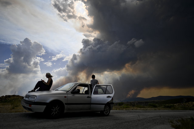 Some people watch the columns of smoke rising from a wildfire in Gois, Coimbra district, on June 20, 2017. The huge forest fire that erupted on June 17, 2017 in central Portugal killed at least 64 people and injured 135 more, with many trapped in their cars by the flames. (Photo by Patricia De Melo Moreira/AFP Photo)