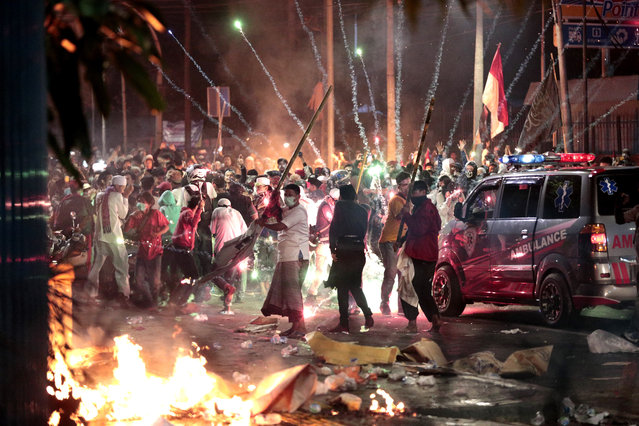 Fire crackers explode near supporters of presidential candidate Prabowo Subianto during clashes with the police in Jakarta, Indonesia, Wednesday, May 22, 2019. Indonesian President Joko Widodo said authorities have the volatile situation in the country's capital under control after six people died Wednesday in riots by supporters of his losing rival in last month's presidential election. (Photo by Dita Alangkara/AP Photo)