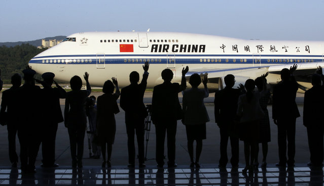 An airplane with Chinese President Xi Jinping and first lady Peng Liyuan on board departs as South Korean officials see them off, at Seoul Military Airport in Seongnam, South Korea, Friday, July 4, 2014. Xi highlighted Japan's brutality against China and South Korea in the last century during a speech on the final day of his visit to Seoul on Friday amid worries in both countries about recent nationalism in Tokyo. (Photo by Lee Jin-man/AP Photo)
