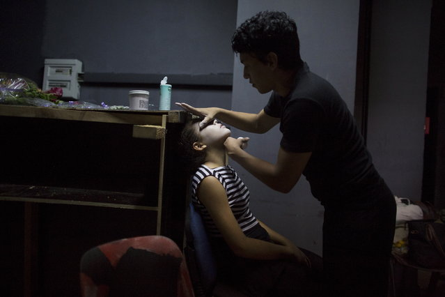 Choreographer Rafael Gonzalez, 31, (R), applies make-up to Sheila Marrupe, 15, at the backstage of the Bertolt Brecht Theatre before performing at the VI International Pantomime Festival Havana 2015, in Havana, June 12, 2015. (Photo by Alexandre Meneghini/Reuters)