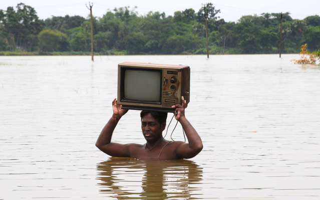 An Indian man carries a television set through flood waters in Howrah district in West Bengal state on August 7, 2015. Rivers have burst their banks, hitting thousands of villages in parts of West Bengal as well as northeastern Manipur state, where roads and bridges have been cut. (Photo by AFP Photo)