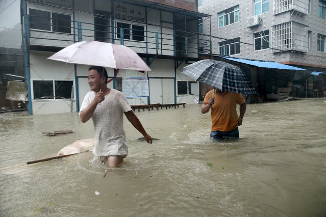 People wade through a flooded street at a town hit by Typhoon Soudelor in Ningde, Fujian province, China, August 9, 2015. (Photo by Reuters/Stringer)