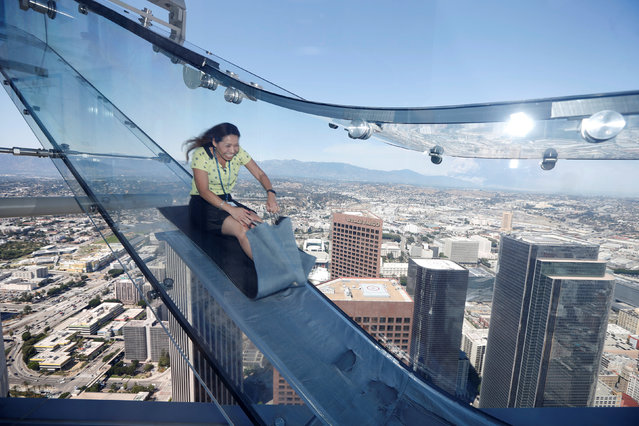 Sandra Brown, 40, rides the Skyslide on the 69th and 70th floors of the U.S. Bank Tower which is attached to the OUE Skyspace LA observation deck in downtown Los Angeles, California, U.S. June 20, 2016. (Photo by Lucy Nicholson/Reuters)