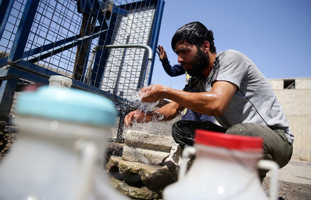 A man washes his head as he fills water containers, in the rebel held besieged town of Douma, eastern Damascus suburb of Ghouta, Syria, June 23, 2016. (Photo by Bassam Khabieh/Reuters)