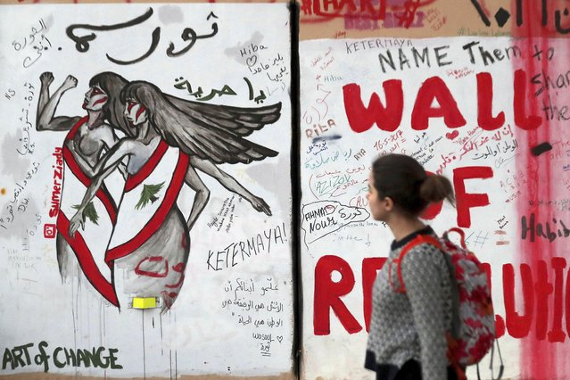 """In this Tuesday, November 26, 2019 photo, a woman looks at a wall at United Nations Headquarters, decorated with graffiti in Arabic that reads, """"Revolution is a woman, and Oh freedom"""", during ongoing protests, in Beirut, Lebanon. Lebanon's wave of anti-government protests has given a new platform for women struggling against religious laws. Under Lebanon's sectarian system, sects have the power to set the rules for marriage, divorce and custody of children for their communities. (Photo by Hassan Ammar/AP Photo)"""