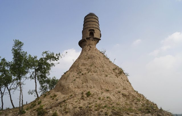 An ancient tower is seen balancing on the top of a dirt hill, with its base slightly eroded, along a grassland in Qixian county, Shanxi province July 19, 2014. Local authorities said they were looking into way to protect and remedy the tower after pictures, taken by a relic preservation enthusiast, were posted on the Internet, local media reported. (Photo by Reuters/Stringer)