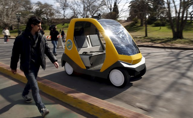 A man walks next to a prototype of an autonomous electric vehicle during its presentation in Buenos Aires, August 19, 2015. The autonomous vehicle, the first of its kind developed in Argentina, is able to fulfill the main functions of mobility of a traditional car but autonomously through the use of artificial intelligence that enables it to detect their surroundings and move without human intervention. (Photo by Marcos Brindicci/Reuters)
