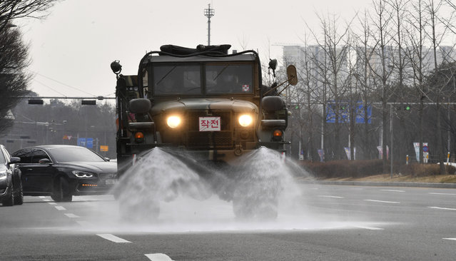 In this February 11, 2020 photo, Soldiers in the military truck, spray disinfectant as a precaution against the COVID-19 on the street in Gwangju, South Korea. The U.S. and South Korean militaries, used to being on guard for threats from North Korea, face a new and formidable enemy that could hurt battle readiness: a virus spreading around the world that has infected more than 1,200 people in South Korea. (Photo by Shin Dae-hee/Newsis via AP Photo)