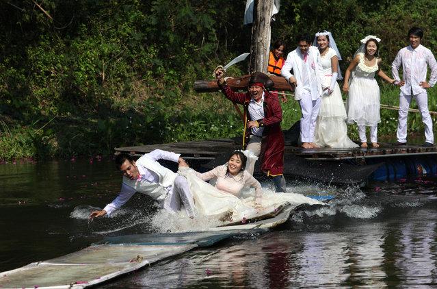 Thai groom and bride, Sorawich Changtor (front L), 28, and Rungnapa Panla (front R), 30, run to escape a man dressed as a pirate as (behind L-R) Prasit Rangsiyawong, 29, Varuttaon Rangsiyawong, 27, Chutima Imsuntear, 37, and Sopon Sapaotong, 41, look on during a wedding ceremony in Prachin Buri province, east of Bangkok February 13, 2013. (Photo by Kerek Wongsa/Reuters)