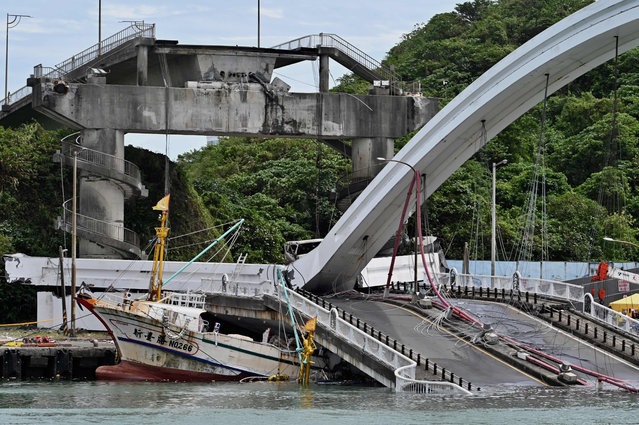 A fishing boat is pictured after it was crushed when a bridge collapsed in the Nanfangao fish harbour in Suao township on October 1, 2019. The bridge collapsed in northeastern Taiwan on October 1 injuring at least 14 people as it smashed down onto fishing vessels moored underneath and sent a petrol tanker plummeting into the water. (Photo by Sam Yeh/AFP Photo)