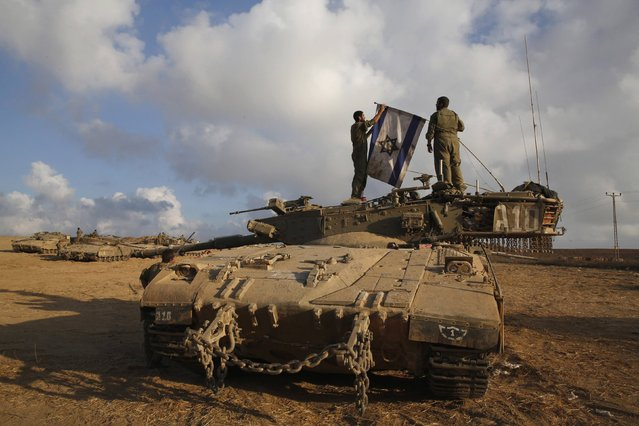 Israeli soldiers place their national flag atop a tank at a staging area near border with the Gaza Strip August 4, 2014. Palestinians accused Israel of breaking its own ceasefire on Monday by launching a bomb attack on a refugee camp in Gaza City that killed an eight-year-old girl and wounded 29 other people. An Israeli military spokeswoman said she was checking the report. (Photo by Baz Ratner/Reuters)