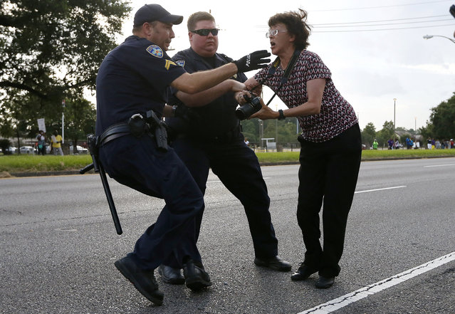 A woman is detained by law enforcement near the headquarters of the Baton Rouge Police Department in Baton Rouge, Louisiana, U.S. July 9, 2016. (Photo by Jonathan Bachman/Reuters)