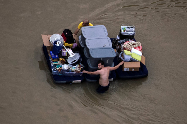 Residents wade with their belongings through flood waters brought by Tropical Storm Harvey in Northwest Houston, Texas, U.S. August 30, 2017. (Photo by Adrees Latif/Reuters)