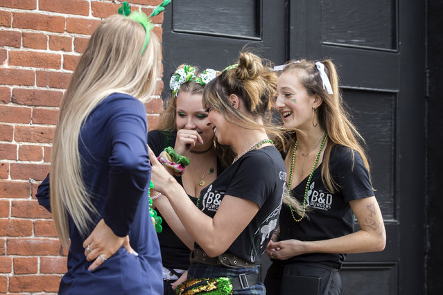 A group of servers from a local hamburger restaurant gather to look at a cell phone photo of themselves in St. Patrick's Day attire, Tuesday, March, 17, 2020, in Savannah, Ga. Last week Savannah's mayor called off the city's 196-year-old St. Patrick's Day parade, but left bars and restaurants open for business. (Photo by Stephen B. Morton/AP Photo)