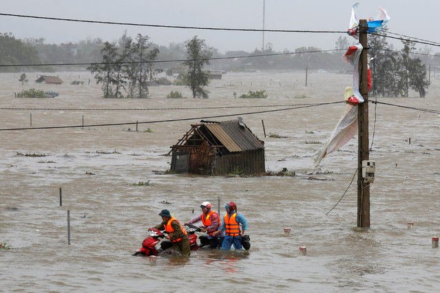 People recover motorbikes from a flooded fields while the Doksuri storm hits in Ha Tinh province, Vietnam September 15, 2017. (Photo by Reuters/Kham)