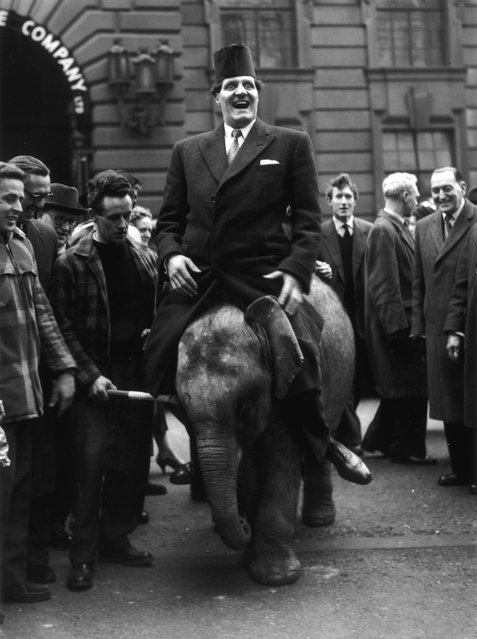 Comic conjuror Tommy Cooper (1922–1984), wearing his trade-mark fez, riding Pioneer, a three year old elephant from Billy Smart's circus, to the opening of a joke and tricks shop in High Holborn. 23rd February 1959. (Photo by Keystone)