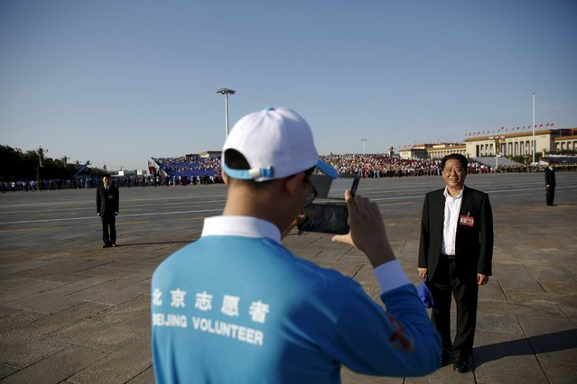 A guest has his picture taken by a volunteer at the Tiananmen Square before a military parade to mark the 70th anniversary of the end of World War Two, in Beijing, China, September 3, 2015. (Photo by Damir Sagolj/Reuters)