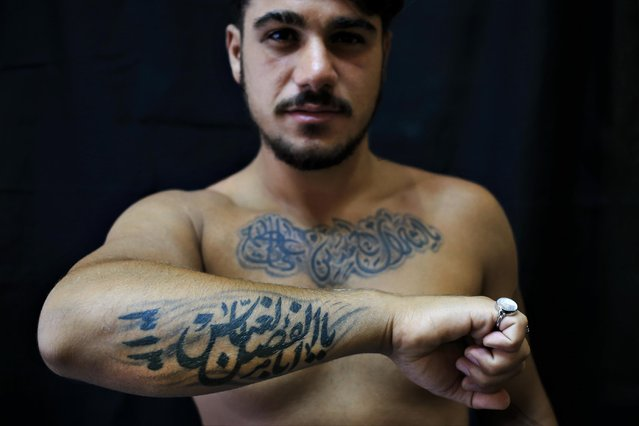"In this Monday, July 18, 2016 photo, Alodi Issa, 22, poses for a photo showing off his tattoos with Shiite Muslim religious slogans in the southern suburb of Beirut, Lebanon. The tattoo in Arabic reads, ""Oh, the revenge for Hussein. Ali, Fatima. 313, Oh Abu Fadel al-Abbas"". (Photo by Hassan Ammar/AP Photo)"