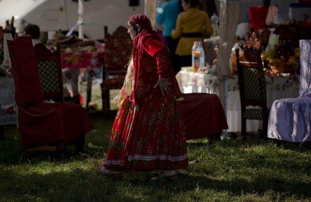 A Roma woman walks as the Roma community celebrates the Birth of the Virgin Mary in Costesti, Romania, Monday, September 8, 2014. (Photo by Vadim Ghirda/AP Photo)