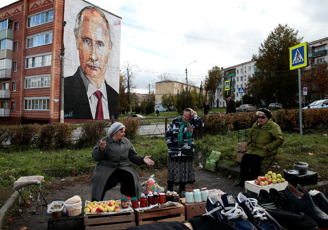 Elderly women wait for customers as they sell their self-made food products at a street market, with a graffiti depicting Russian President Vladimir Putin on the wall of a house seen in the background, in the town of Kashira, outside Moscow, Russia October 10, 2017. (Photo by Andrey Volkov/Reuters)