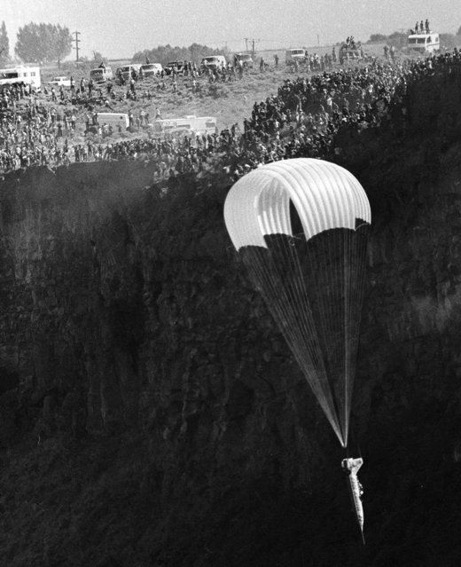 Evel Knievel parachutes down in a rocket after an ill-fated attempt to soar across the Snake River Canyon in Twin Falls, Idaho, on September 8, 1974. The jump failed when the parachute on his rocket malfunctioned, opening prematurely. Knievel was uninjured. (Photo by AP Photo)