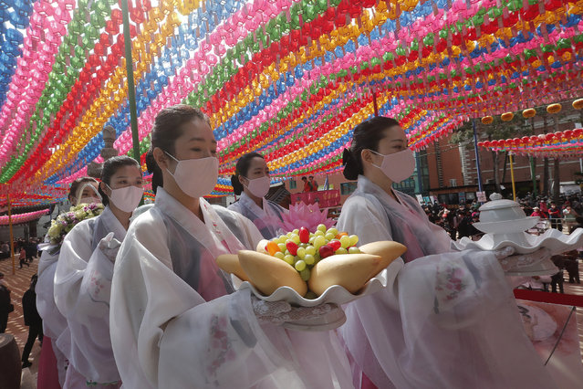 Buddhist believers wearing faces masks to help protect against the spread of the new coronavirus wait to attend a service to pray for overcoming the COVID-19 outbreak and to celebrate Buddha's birthday at the Chogyesa temple in Seoul, South Korea, Thursday, April 30, 2020. (Photo by Ahn Young-joon/AP Photo)
