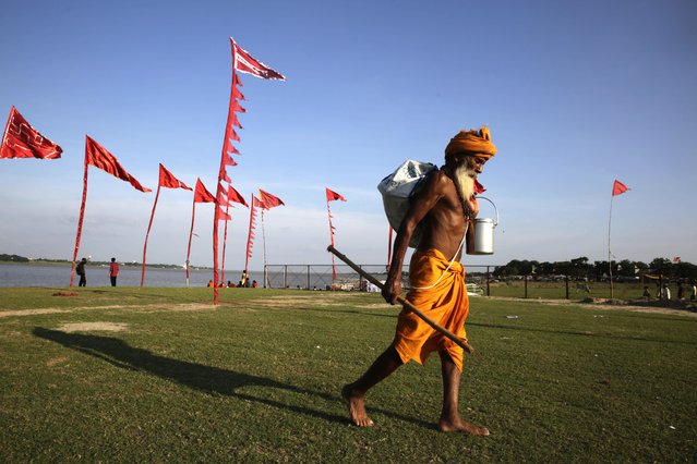 A Hindu holy man or Sadhu walks back to his ashram after taking a dip at Sangam, confluence of Ganges river, Yamuna river and mythical Saraswati river in Allahabad, India, Thursday, August 4, 2016. (Photo by Rajesh Kumar Singh/AP Photo)