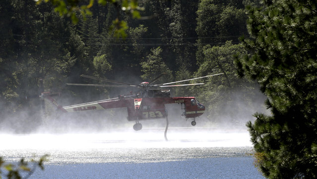 A Skycrane helicopter refills its tanks with water to battle the King Fire near Pollack Pines, Calif., Monday, September 15, 2014. The fire, which started Sunday has consumed more than 3,000 acres and forced the evacuation of dozens of homes. (Photo by Rich Pedroncelli/AP Photo)